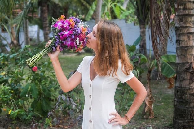 花の花束を保持している白いドレスの女性。