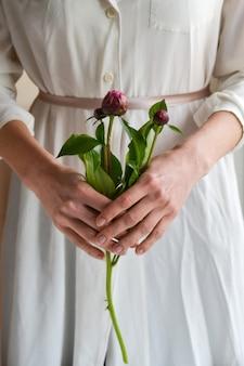 ピンクの牡丹ボタンの花を保持している白いドレスの女性。閉じる