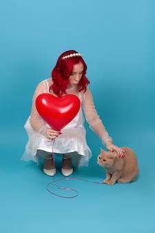 Женщина в белом платье держит летающий воздушный шар в форме сердца, гладит рыжего британского кота