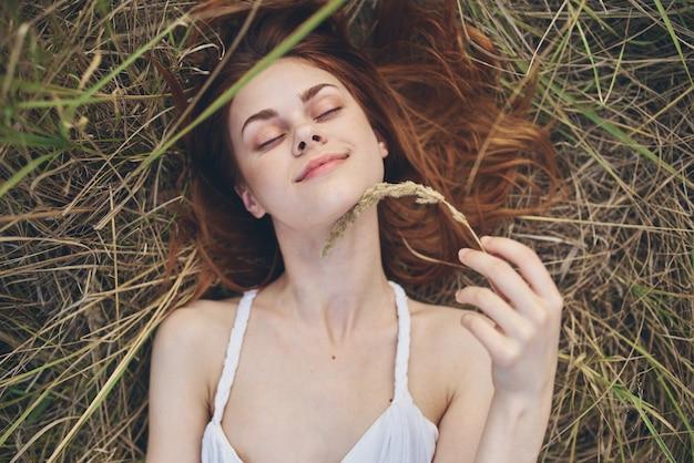 白いドレスを着た女性は、草の自然の休暇の夏に横たわっています。高品質の写真