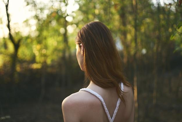 白いドレスの自然の中の女性は森の夏の木を歩く Premium写真