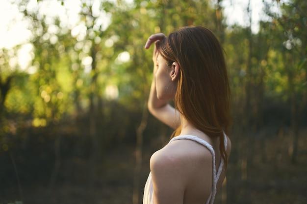 白いドレスの自然の中の女性は森の夏の木を歩く