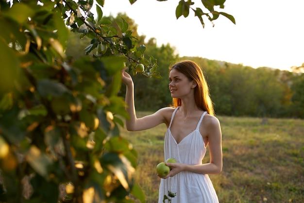 リンゴの木の自然の夏の近くの白いドレスの女性