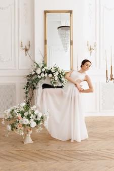 클래식 스튜디오에서 꽃 근처 흰색 드레스 여자