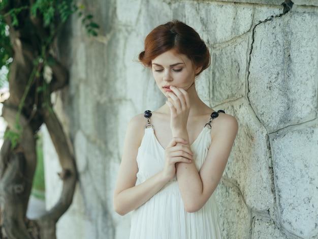 ギリシャの装飾で屋外の白いドレスの女性