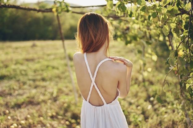 リンゴの木の旅行の自由の近くの屋外で白いドレスを着た女性
