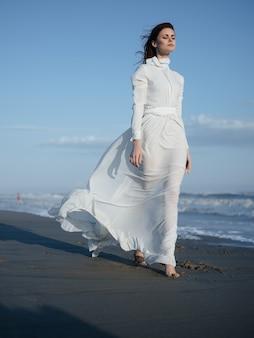 ビーチでの休暇に沿って歩くファッションをポーズする白いドレスの女性