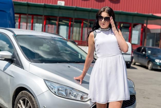 Женщина в белом платье позирует возле машины