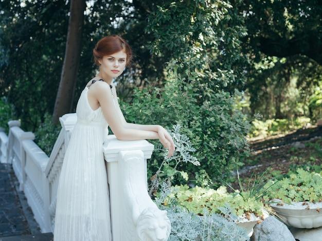 公園自然夏ギリシャのポーズをとる白いドレスの女性