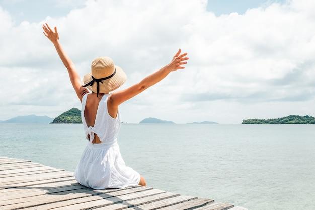Женщина в белом платье сидит в одиночестве на пристани. вид сзади