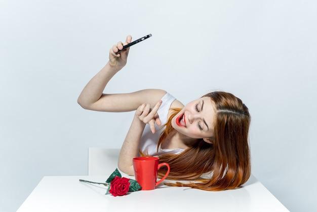 Женщина в белом платье сидит за столом и делает селфи с телефоном