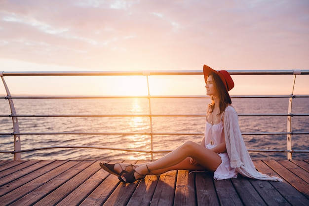 Женщина в белом платье сидит на берегу моря на восходе солнца в романтическом настроении в красной шляпе