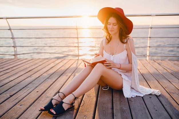 Женщина в белом платье сидит на берегу моря на восходе солнца, думает и делает заметки в дневнике в романтическом настроении в красной шляпе
