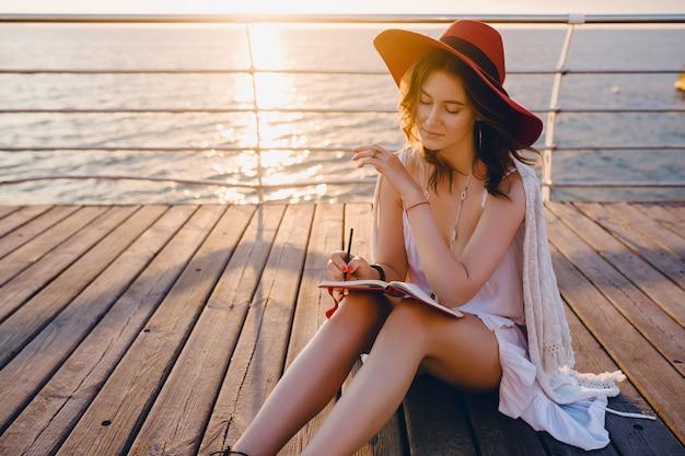 赤い帽子をかぶっているロマンチックな気分で日の出を考えて日記の本でメモをとることで海のそばに座っている白いドレスを着た女性