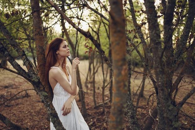 白いドレスの木の女性夏は新鮮な空気を歩く