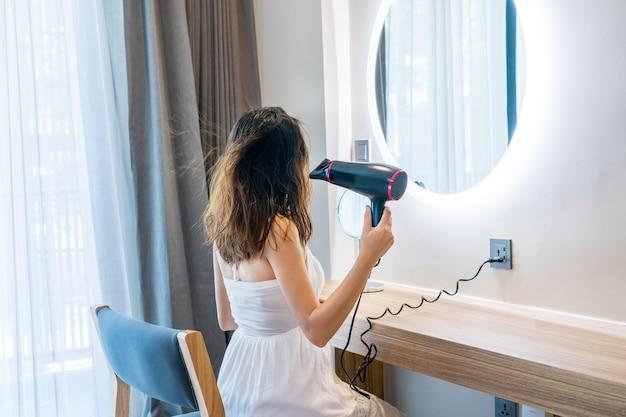 아침에 머리를 씻은 후 헤어 드라이어를 사용하여 흰 드레스 여자. 공간 복사