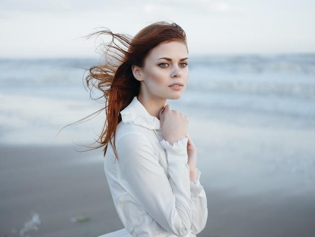 ビーチの海の休暇に沿って歩く白いドレスの女性