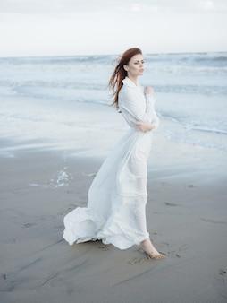 砂の海の新鮮な空気の旅を裸足で歩く白いドレスの女性