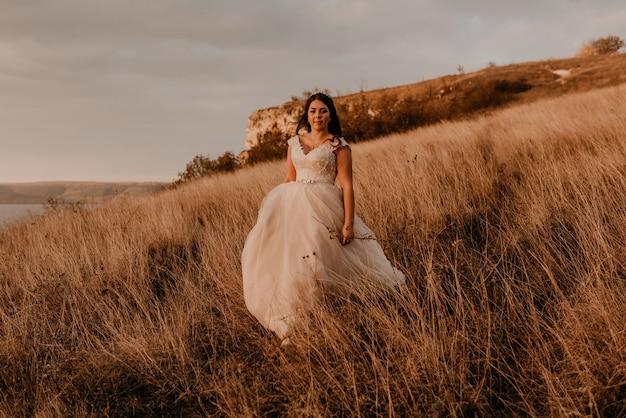 Женщина в белом платье идет по высокой траве в поле