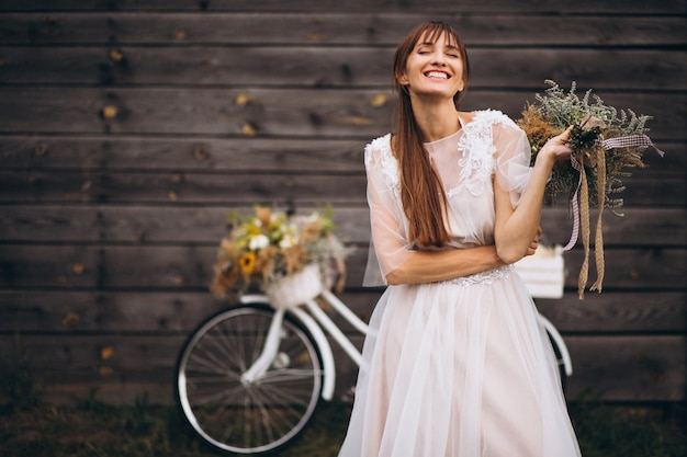 Женщина в белом платье с велосипедом у деревянной стены