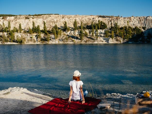 川の自然の休暇旅行の近くの白い帽子の女性。高品質の写真
