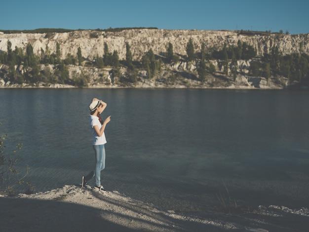 Женщина в белой шляпе возле реки природа отпуск путешествия