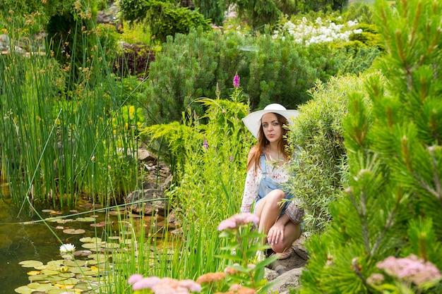 다양한 식물이 있는 호수 근처의 바위에 앉아 있는 흰 모자를 쓴 여성, 다른 나무의 배경을 가진 공원의 꽃