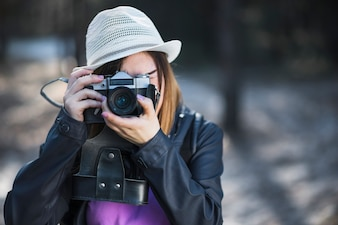 Woman in white hat taking pictures