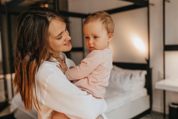흰색 집 복장에있는 여자 아이를 바라보며 그녀를 팔에 보유하고 있습니다. 딸은 침대의 배경에 엄마를 만진다.
