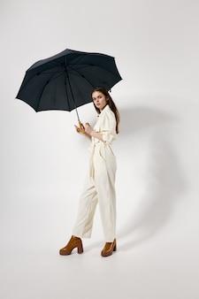 白いジャンプスーツの茶色の靴と開いた傘のファッションの分離された女性
