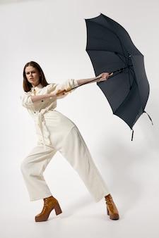 開いた傘と白いジャンプスーツの女性