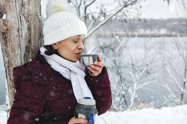 熱いお茶を飲みながら美しい雪の日を楽しんでいる白いニットウールの帽子の女性。降る雪