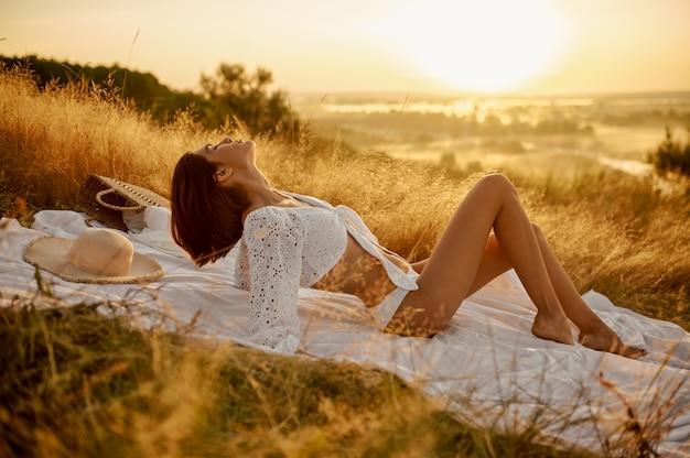 フィールドで毛布に白いランジェリーの女性