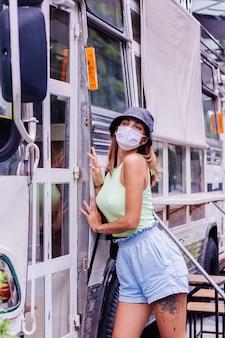 白い医療マスクの女性が街を歩く街の広場のバスカフェのそばに立つ