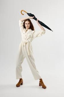 雨のスタジオから彼女の頭の保護の上に傘を持っている白いオーバーオールの女性
