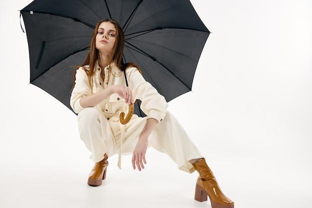 열린 우산 근접 촬영으로 쪼그리고 흰색 바지에 여자