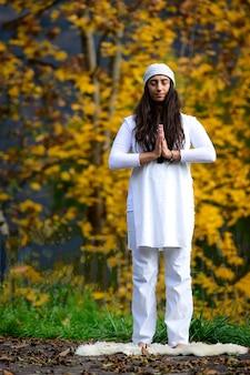 Женщина в белом занимается йогой на природе осенью
