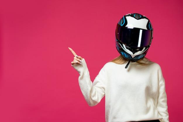 オートバイのヘルメットと白いプルオーバーの女性