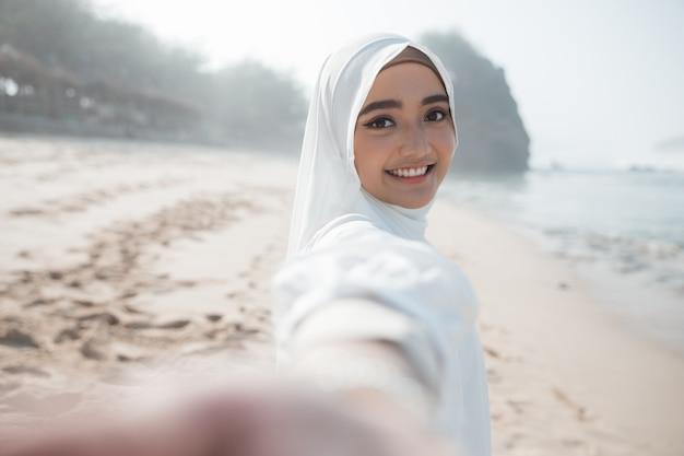 Женщина в белом шарфе принимает селфи