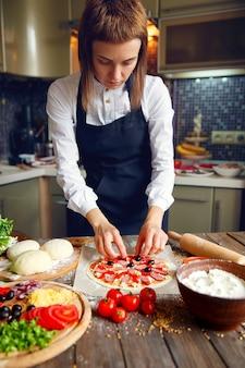 白いシャツとエプロンの女性がピザに材料を置く