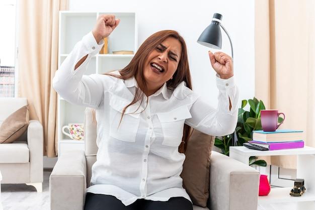 白いシャツと黒いズボンを着た女性が、明るいリビング ルームの椅子に座ってイライラした狂った握りこぶしを上げている