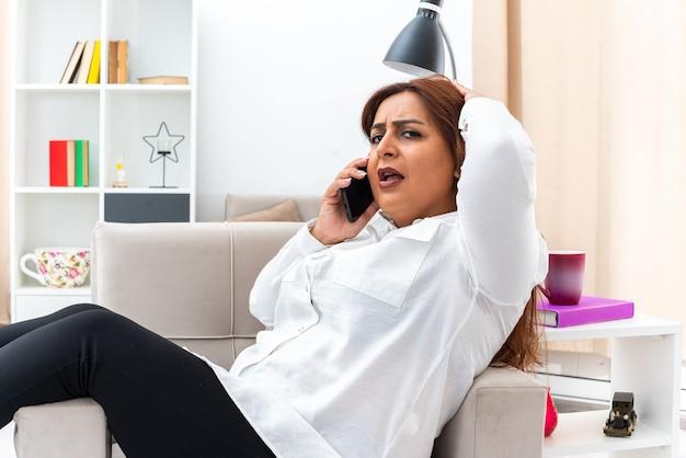 밝은 거실의 의자에 앉아 휴대 전화로 이야기하는 동안 흰 셔츠와 검은 색 바지를 입은 여성이 혼란스럽고 불쾌한 모습을 보입니다.