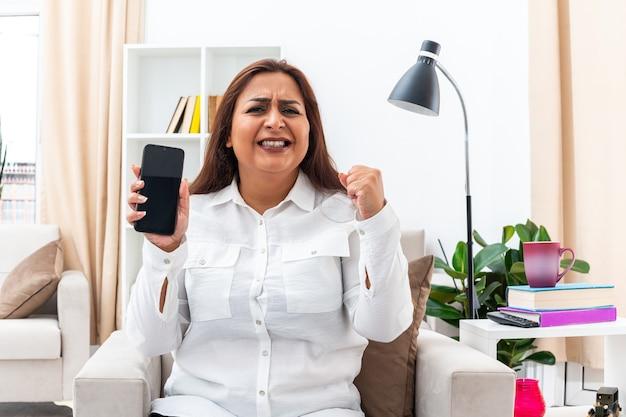 Женщина в белой рубашке и черных штанах сидит на стуле со смартфоном, сжимая кулак, сердитая и разочарованная в светлой гостиной