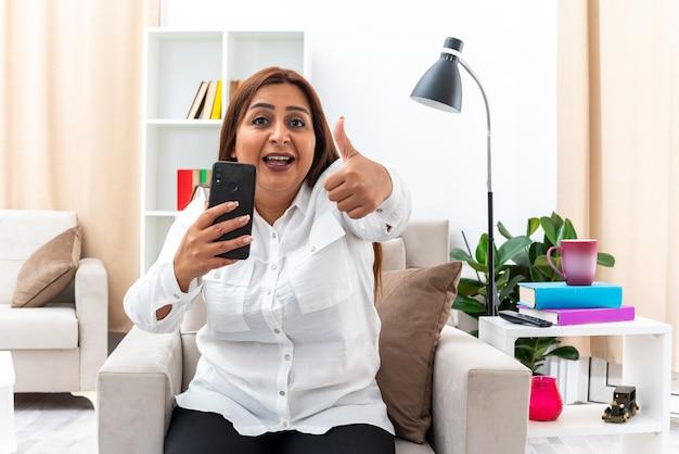 白いシャツと黒いズボンを着た女性がスマートフォンを持ち、明るいリビングルームの椅子に座って幸せでポジティブな笑顔を見せる