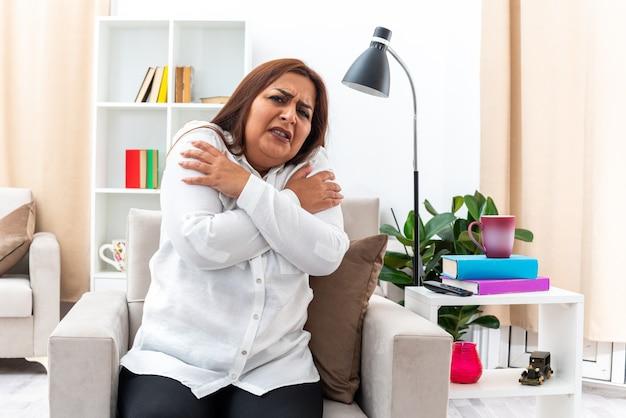 흰 셔츠와 검은 색 바지를 입은 여성이 걱정하고 가벼운 거실의 의자에 앉아 무서워합니다.
