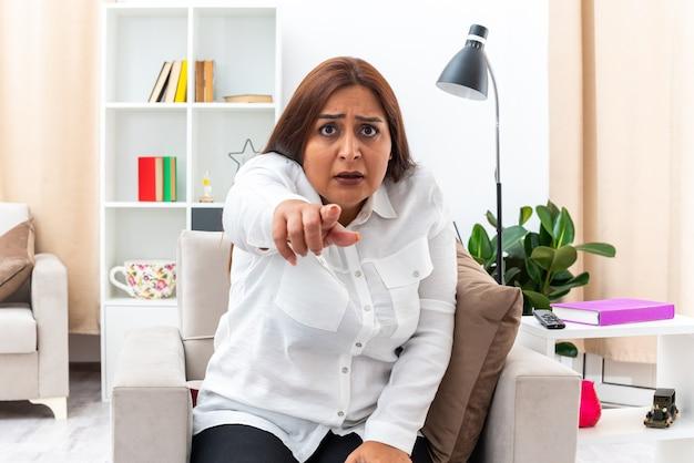 白いシャツと黒いズボンを着た女性が、明るいリビング ルームの椅子に座っている人差し指で心配している
