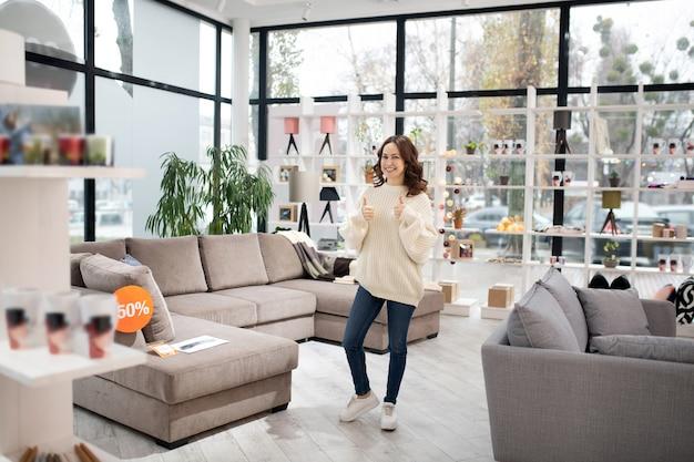 Женщина в белой рубашке и джинсах выбирает модели в мебельном салоне