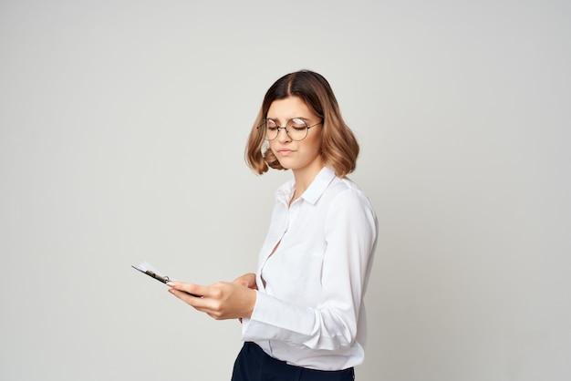 白いシャツを着た女性のドキュメントは、成功スタジオで動作します。高品質の写真