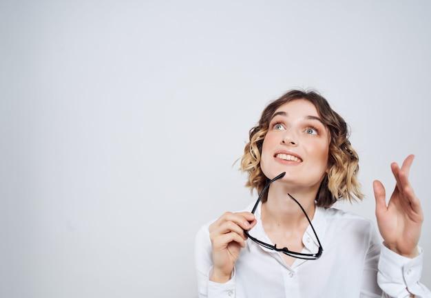 白いシャツの感情のオフィススタジオの明るい背景の実業家の女性