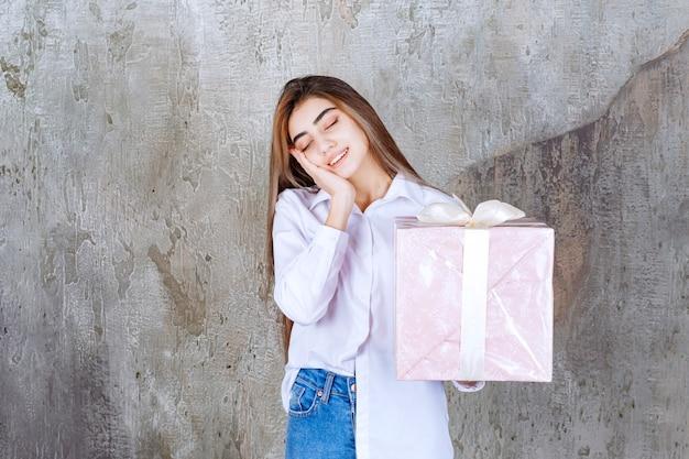 白いリボンで包まれたピンクのギフトボックスを保持し、疲れて眠い感じの白いシャツを着た女性。